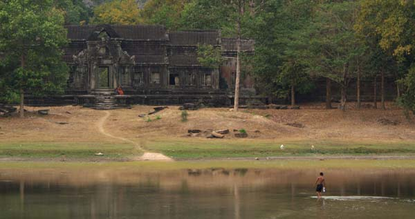 Photograph of a man carrying water across Angkor Wat's main moat in the dry season to a monk sitting on the steps of an entrance point to the main grounds