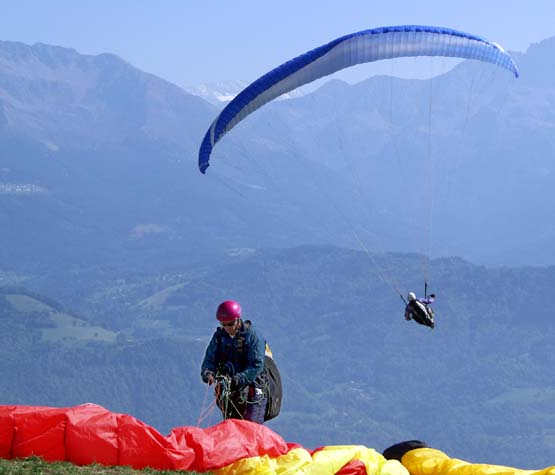Photograph of a paraglider preparing to launch his red wing, a bright yellow wing rests on the ground to the right of the image. Already airborne a blue wing is set against the dramatic St Hilaire mountains and woodland.